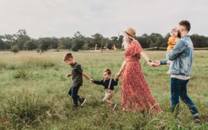 Life Insurance - Family Walking Through Grass During a Festival